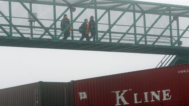 Workers cross a bridge on their return to work at the Port of Long Beach on Wednesday.