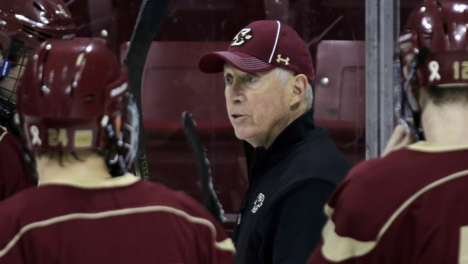 Boston College hockey coach Jerry York, center, talks with his players during an NCAA college hockey practice in Boston.