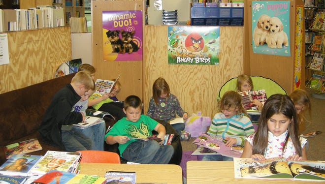Students look through books during reading time in the library.