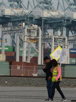 Striking workers carry placards past cranes sitting idle by shipping containers Dec. 4, 2012, at the Port of Los Angeles.