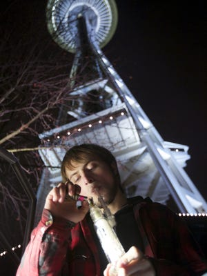 Paul, who declined to give his last name, of Tacoma, Wash., smokes marijuana from a water pipe underneath the Space Needle shortly after a law legalizing the recreational use of  marijuana took effect in Seattle.