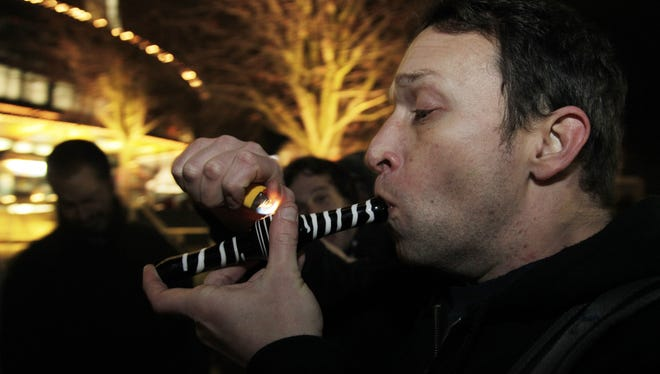 Gary Parrish smokes marijuana in a glass pipe on Thursday at the Space Needle in Seattle, Wash.
