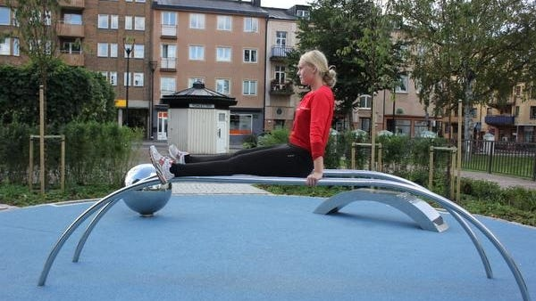 A woman works out on public exercise equipment at City Art Gym in the main square of Ängelholm, Sweden.