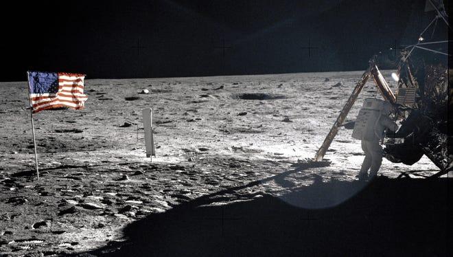 Astronaut Neil Armstrong walks on the moon.