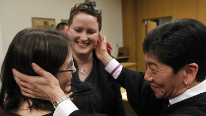Judge Mary Yu, right, congratulates Emily Cofer, left, and Sarah Cofer after declaring them wed moments after midnight in the King County Courthouse. The Cofers were the first same-sex couple to legally marry in Washington.