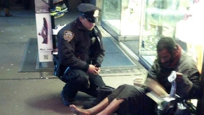 New York City Police Officer Larry DePrimo giving boots to Jeffrey Hillman on  Nov. 14, 2012 in Times Square.