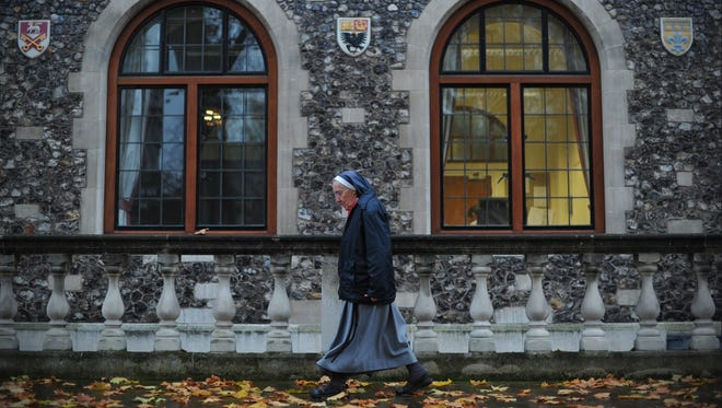 """A nun walks to the venue of the three-day Church of England General Synod in central London in November. The British government announced a ban on the Church of England offering same-sex marriages, but will allow other religious organizations to """"opt in"""" to holding gay ceremonies."""
