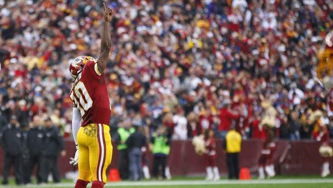 Washington Redskins quarterback Robert Griffin III (10) celebrates after throwing a touchdown pass against the Baltimore Ravens in the first quarter at FedEx Field. The Redskins won 31-28 in overtime.