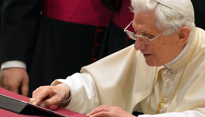 Pope Benedict XVI uses a tablet to send his first Twitter message during his weekly general audience Wednesday.