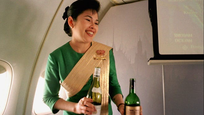 In this Dec. 14, 1996, file photo, a Thai Airways International flight attendant offers a passenger a selection of wine during a flight from Singapore to Bangkok.