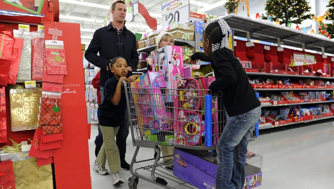 """Atlanta Falcons quarterback Matt Ryan helps children push a cart of toys while he and teammates participated in the """"Shop with a Jock"""" program, which provides a $100 gift card and a shopping experience to children from an Atlanta-area mission at a Walmart department store, Tuesday, Dec. 11, 2012, in Suwanee, Ga."""