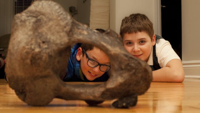 From left, Eric Stamatin, 11, of  Shelby Township, MIch., and his cousin Andrew Gainariu, 11, of Troy are photographed with the 13,000 to 14,000-year-old American mastodon axis bone they found near Eric's house Tuesday, Dec. 11, 2012.