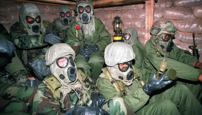 Soldiers with the U.S. Army's 7th Corps huddle in a bunker in Eastern Saudi Arabia with gas masks and chemical suits following the start of the 1991 Persian Gulf War.