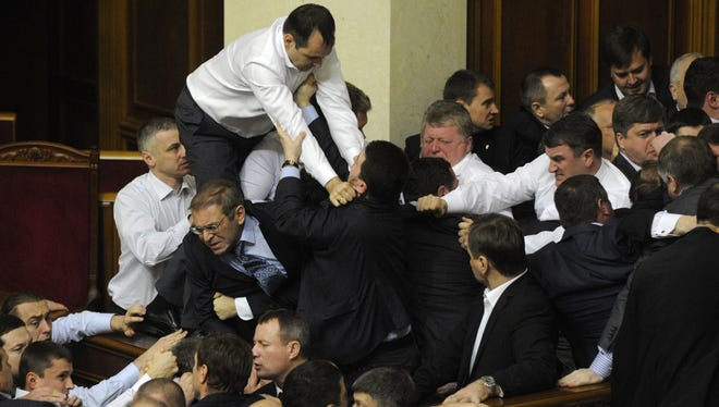 Ukrainian lawmakers fight around the rostrum during the first session of Ukraine's newly elected parliament in Kiev, Ukraine, Thursday.