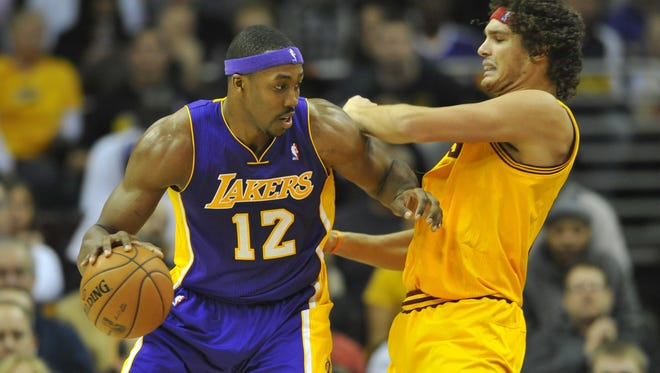 Los Angeles Lakers center Dwight Howard (12) drives against Cleveland Cavaliers center Anderson Varejao (17) in a recent game. Howard says he's not 100 percent healthy right now.