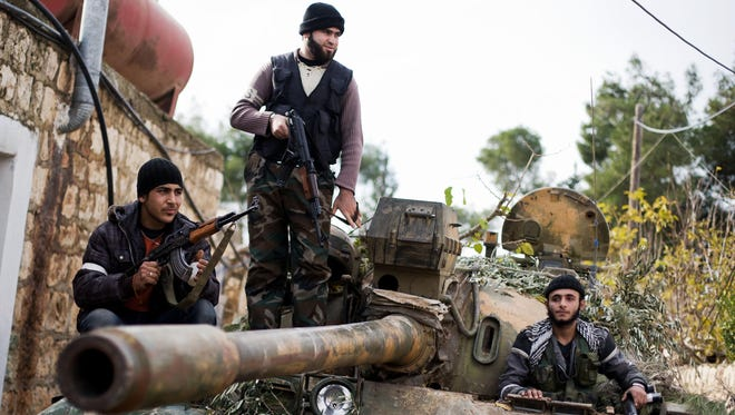 Kurdish members of the FSA are seen on a tank stolen from the Syrian Army in Aleppo, Syria.