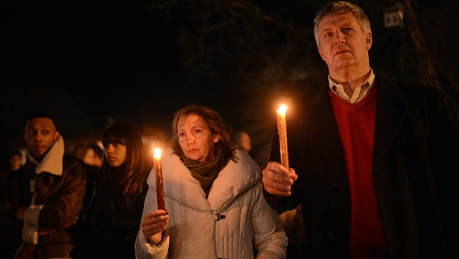 People gather for a prayer vigil at St Rose Church  in Newtown, Conn., hours after a shooting spree at a local school left 26 people, including 20 children, dead.