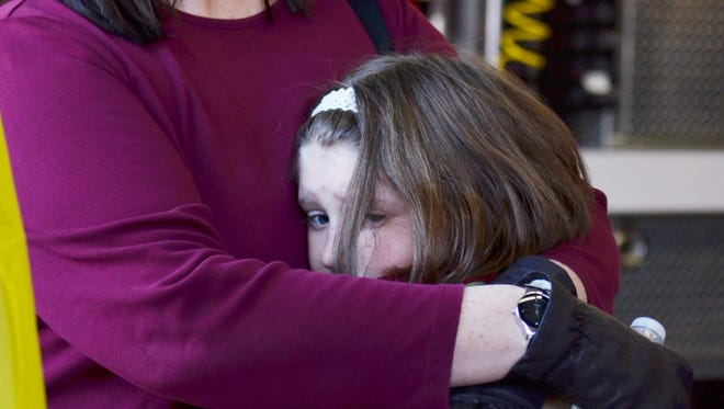 A mother hugs her daughter following a shooting at the Sandy Hook Elementary School in Newtown, Conn.