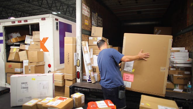 FedEx employee, Ron Shaheen, loads items being shipped into a truck for delivery in Doral, Fla.