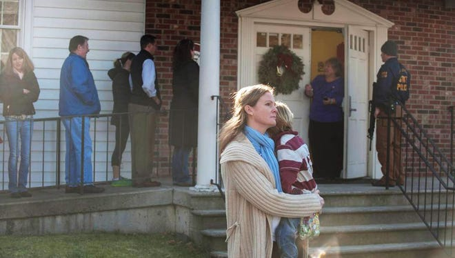 A woman holds a child as people line up to enter the Newtown Methodist Church near the scene of an elementary school shooting in Newtown, Conn.