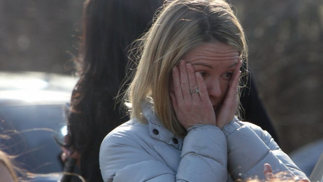 A woman arrives to pick up her children at the Sandy Hook Elementary School in Newtown, Conn., of Friday after a mass shooting.