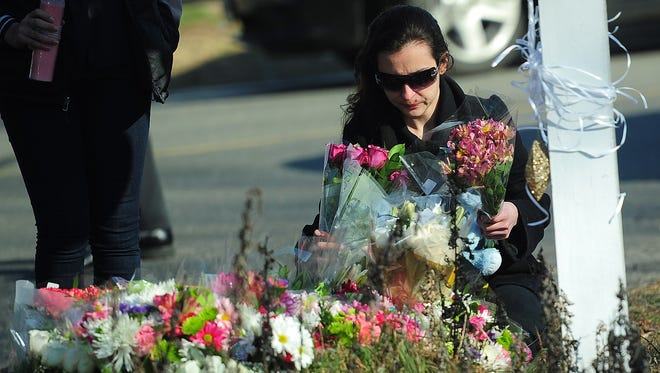 A resident pays tribute to the victims of an elementary school shooting in Newtown, Conn., on Saturday.