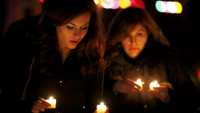 Katy Caulfield, left, and her mother, Irene Caufield, hold candles to place at a makeshift memorial Saturday near the elementary school where a day earlier a gunman opened fire in Newtown, Conn.