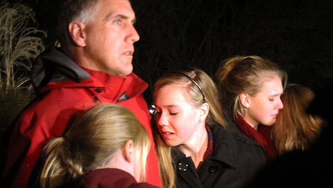 A man hugs his young daughters as they attend a gathering at Saint Rose of Lima church in Newtown where a vigil was held following the deadly school massacre that took place at the Sandy Hook Elementary School Dec. 14, 2012.
