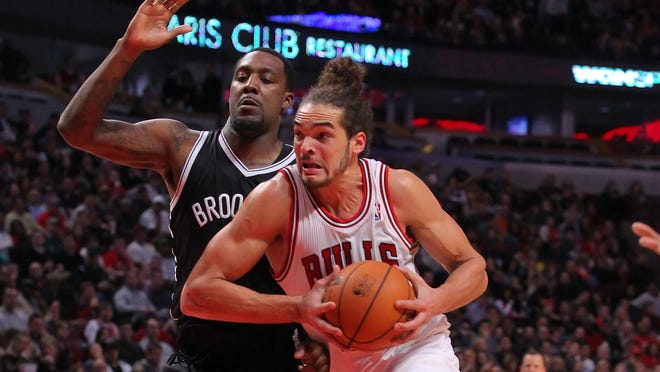 Bulls center Joakim Noah (13) drives past Nets power forward Andray Blatche (0) during the second half at the United Center. The Bulls won 83-82.