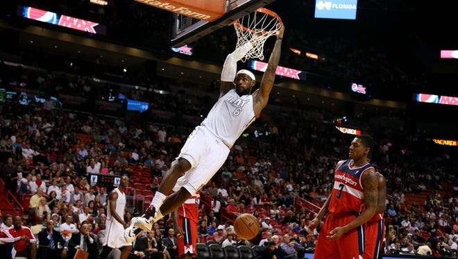 LeBron James dunks the ball over the Wizards' Bradley Beal (3) in the second half of the Heat's 102-72 win Saturday at American Airlines Arena.