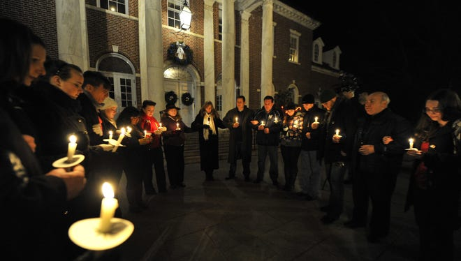 A candlelight prayer service is held Saturday night in front of Edmond Town Hall in Newtown, Conn.