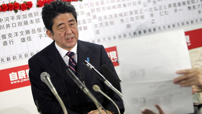 Japan's main opposition Liberal Democratic Party leader Shinzo Abe answers a reporter's question Sunday night at party headquarters in Tokyo.