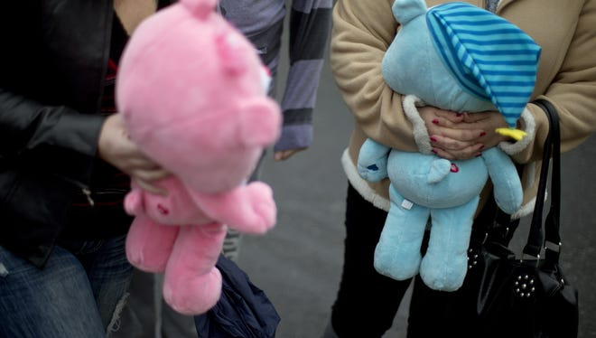 Natalie Zahra, of Vineland, N.J., right, and Amy Zimmerman, of Fairton, N.J., bring teddy bears to a sidewalk memorial for the Sandy Hook Elementary School shooting victims.