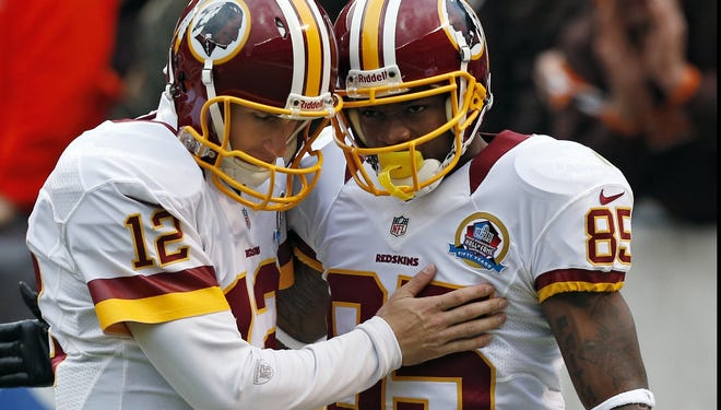 Washington Redskins quarterback Kirk Cousins congratulates wide receiver Leonard Hankerson after a 54-yard touchdown pass in the first quarter of an NFL football game against the Cleveland Browns in Cleveland, Sunday, Dec. 16, 2012.
