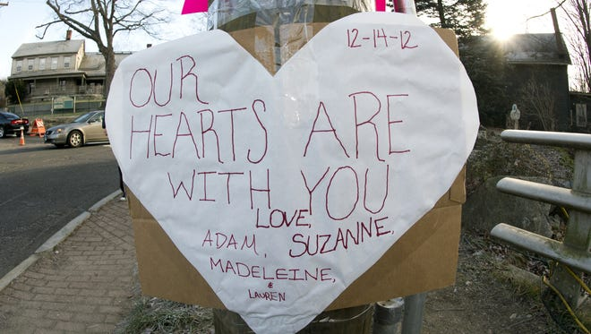 A sign for the victims of the Sandy Hook Elementary School shooting is posted in the Newtown, Conn., on Saturday.