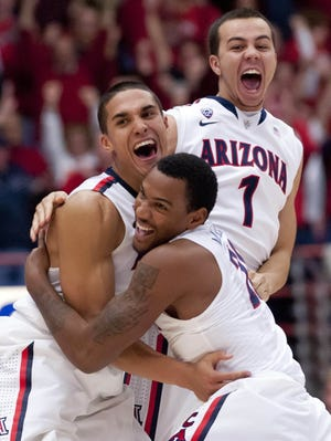 Arizona's Nick Johnson (13), guard Jordin Mayes (20), and guard Gabe York (1) celebrate at the end of the game.