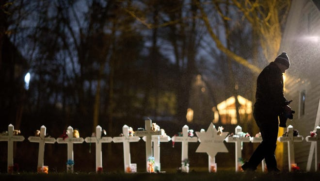 Frank Kulick walks past a display of wooden crosses and a Jewish Star of David, representing the victims of the Sandy Hook Elementary School shooting, on his front lawn on Monday in Newtown, Conn.