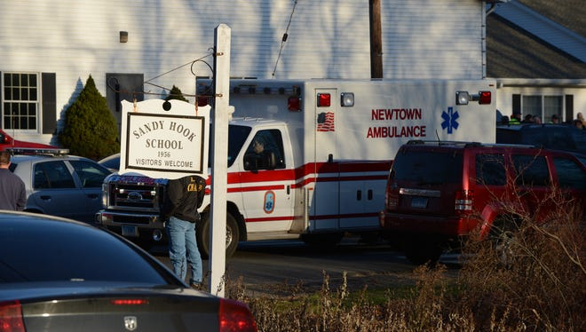 Police and ambulances arrive at the scene of a school shooting at Sandy Hook Elementary School in Newtown, Conn., on Friday.