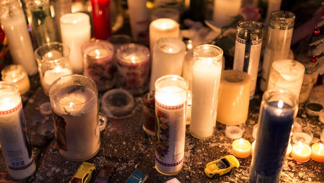 Toy cars are seen with candles at a makeshift memorial on Tuesday in Newtown, Conn.