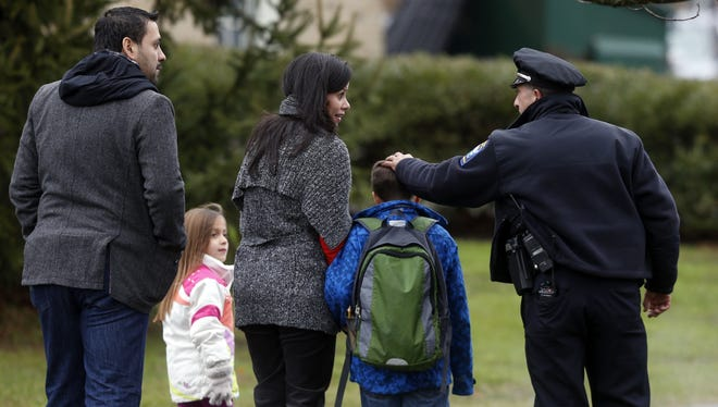 Easton police officer J. Sollazzo greets a returning student as he is walked into Hawley School on Tuesday in Newtown, Conn.