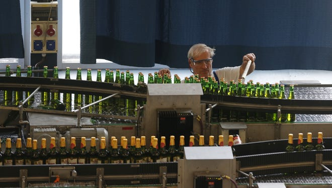 A worker examines bottles of beer at the Budejovicky Budvar brewery, in Ceske Budejovice, Czech Republic.
