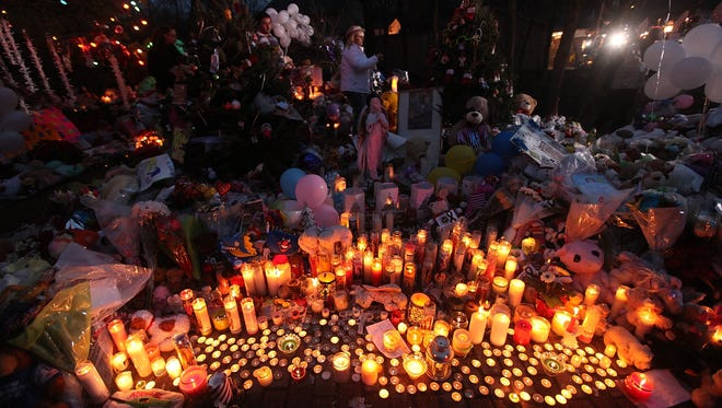 Candles are lit among mementos at a memorial for victims of the mass shooting at Sandy Hook Elementary School Monday in Newtown, Conn.