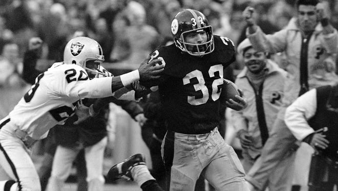 "Franco Harris (32) of the Pittsburgh Steelers eludes tackle by Jimmy Warren of the Oakland Raiders on a 42-yard run to score the winning touchdown in the American Conference playoff game in Pittsburgh, Sunday, Dec. 23, 1972.  Harris' ""Immaculate Reception"" came when a desperation pass to a teammate bounced off a Raiders defender.  The touchdown gave Pittsburgh a 13-7 lead with five second left in the game."