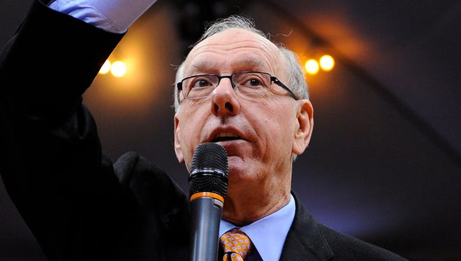 Syracuse men's basketball coach Jim Boeheim speaks to the Carrier Dome audience following his 900th career victory Monday night in Syracuse, N.Y. Later, in his post-game news conference, he advocated for gun control.