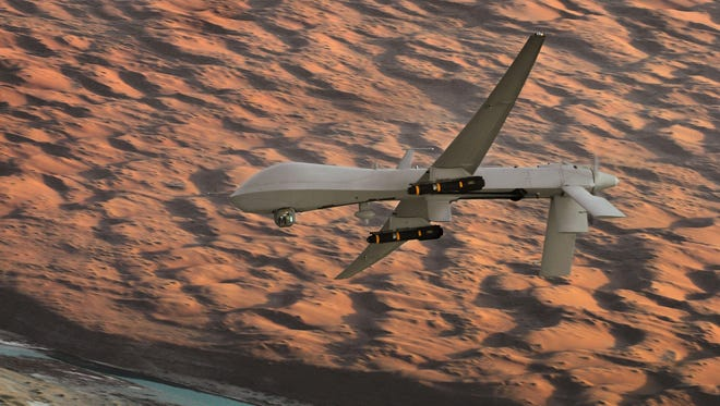 An MQ-1 Predator unmanned aircraft, armed with AGM-114 Hellfire missiles, flies a combat mission over southern Afghanistan.