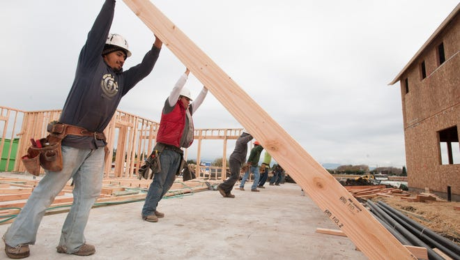 Construction workers raise a wall on a new home at the Estates at Sunnyvale development in California.