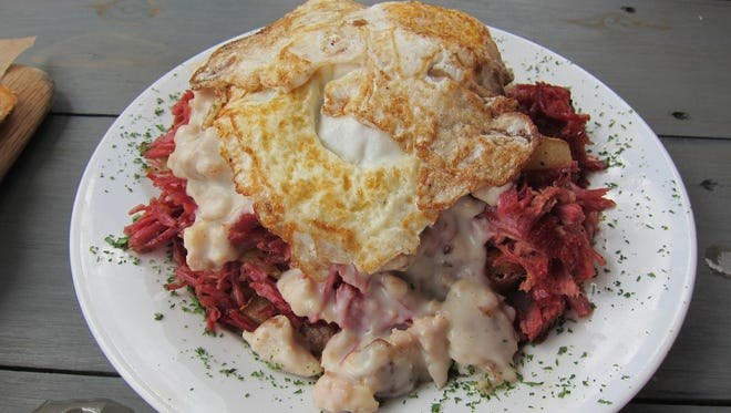 A signature dish, the ?S@#^ on a Shingle? is a huge pile of the delicious house-made corned beef hash topped with elk-sausage gravy, eggs and served with buttermilk biscuits.