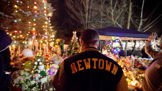 Greg Frattaroli, 19, of Newtown, Conn., visits a memorial for the Sandy Hook Elementary School shooting victims on Tuesday. A week ago, a gunman killed 26 at the school.