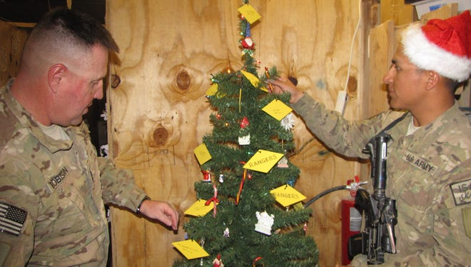 First Sgt. Alan Robison, left, and Spc. David Romero decorate their Christmas tree at Forward Operating Base Arian in Ghazni province.