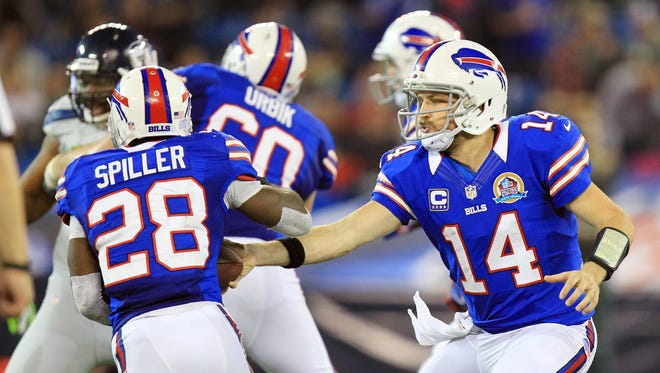 Buffalo Bills quarterback Ryan Fitzpatrick (14) hands off to running back C.J. Spiller against the Seattle Seahawks in a game in Canada. A new stadium agreement has assured that the team will stay in Buffalo until at least 2020.
